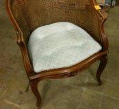 Старинное полукруглое кресло с плетеной спинкой.