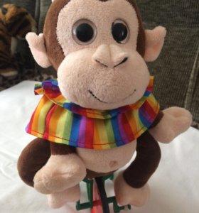 Игрушка обезьянка едит на велосипеде и поёт музыку
