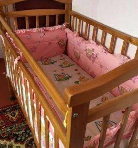 Детская кроватка с матрасом и бортиками.
