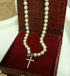 Жемчужное ожерелье с золотым крестиком.