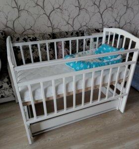 Детская кроватка с матрасом и ящиком для белья.