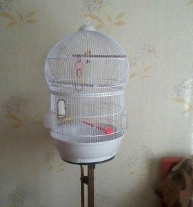 Круглая клетка для птиц на подставке.