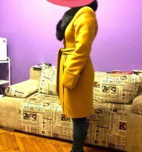 Горчичное пальто с черным меховым воротником.