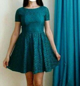 Кружевное платье изумрудного цвета.