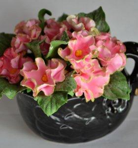 Розовые фиалки в керамическом горшочке.