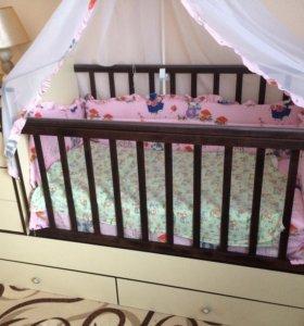 Кроватка детская с ящиками для вещей и маятником.